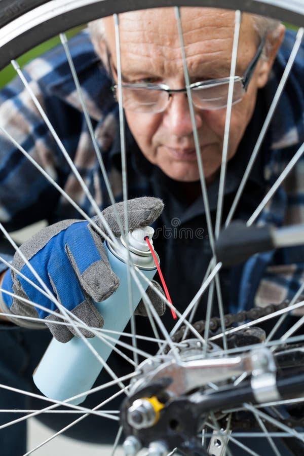 Homem que limpa e que lubrifica uma corrente da bicicleta foto de stock royalty free