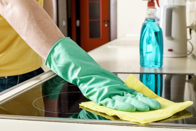 Homem que limpa o fogão na cozinha foto de stock royalty free