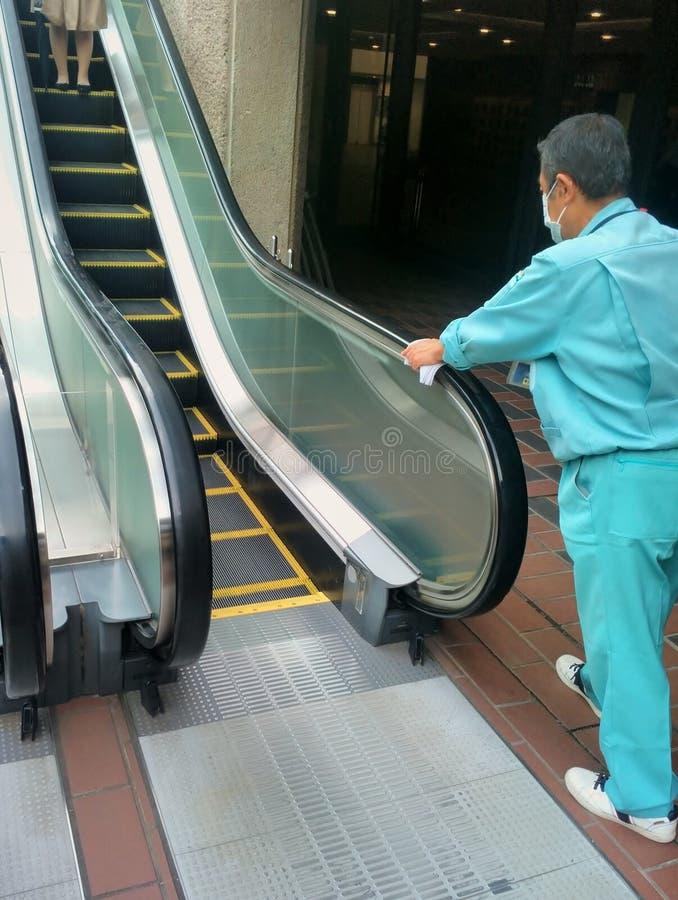 Homem que limpa os perigos da escada rolante Tokyo, Japão imagem de stock royalty free