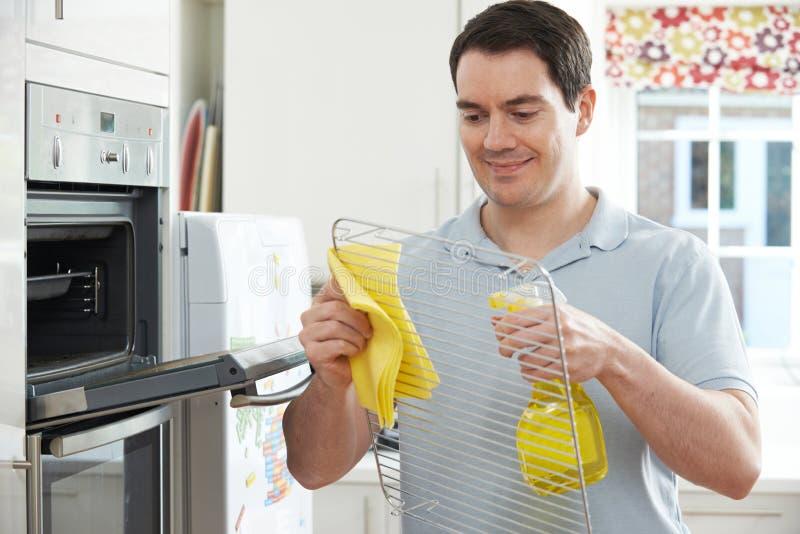 Homem que limpa Oven In Kitchen doméstico fotografia de stock
