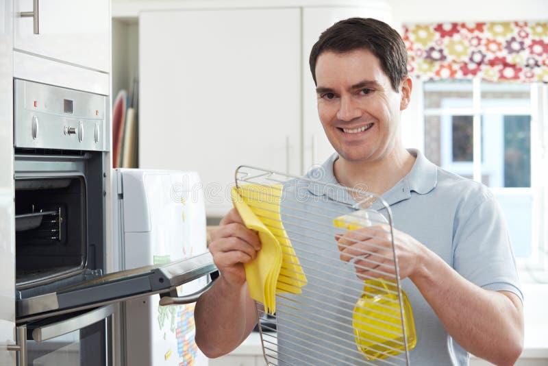 Homem que limpa Oven In Kitchen doméstico imagens de stock royalty free