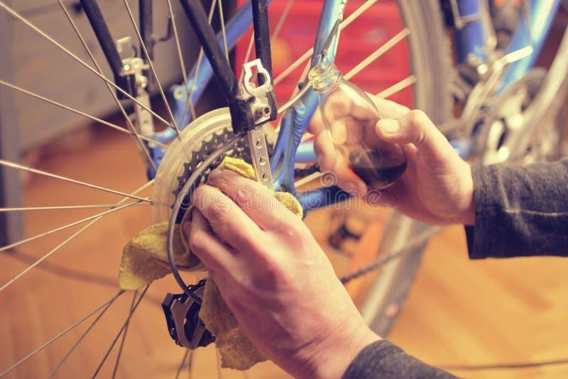 Homem que lubrifica a corrente da bicicleta e que mantém para a estação nova Lubrificação e reparação da movimentação da biciclet foto de stock royalty free