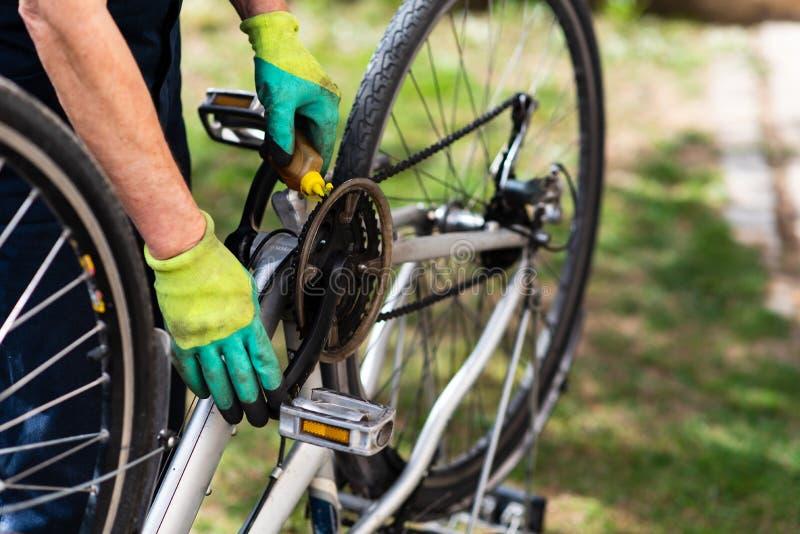 Homem que lubrifica a corrente da bicicleta que mantém para a estação nova imagem de stock royalty free
