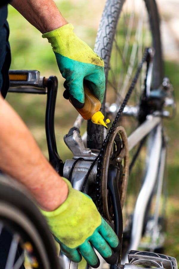 Homem que lubrifica a corrente da bicicleta que mantém para a estação nova fotos de stock royalty free