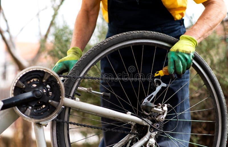Homem que lubrifica a corrente da bicicleta que mantém para a estação nova fotografia de stock royalty free