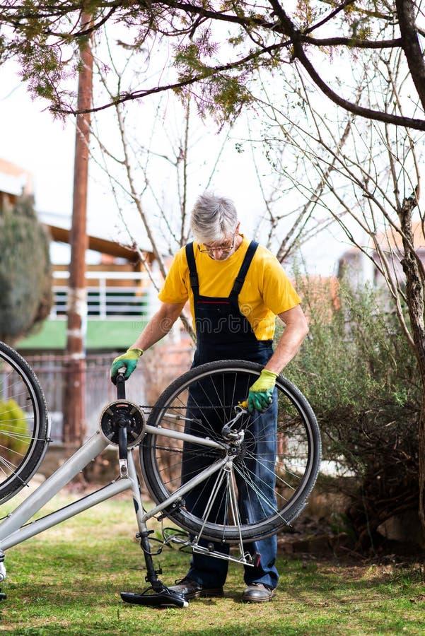 Homem que lubrifica a corrente da bicicleta que mant?m para a esta??o nova fotografia de stock royalty free