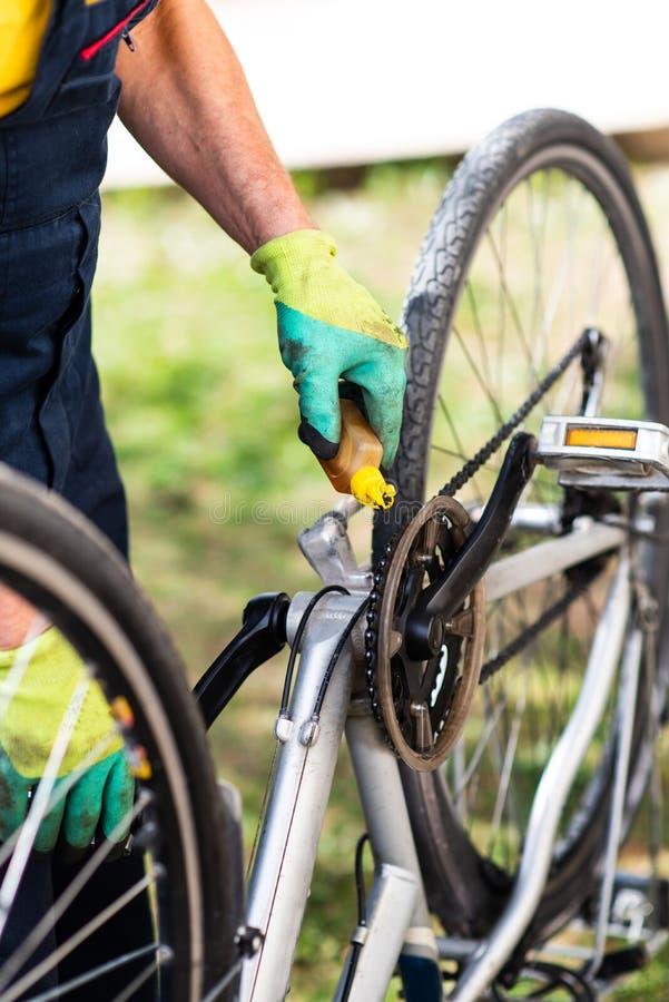 Homem que lubrifica a corrente da bicicleta que mant?m para a esta??o nova fotos de stock royalty free