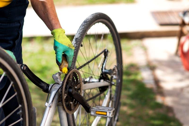 Homem que lubrifica a corrente da bicicleta que mant?m para a esta??o nova imagens de stock royalty free