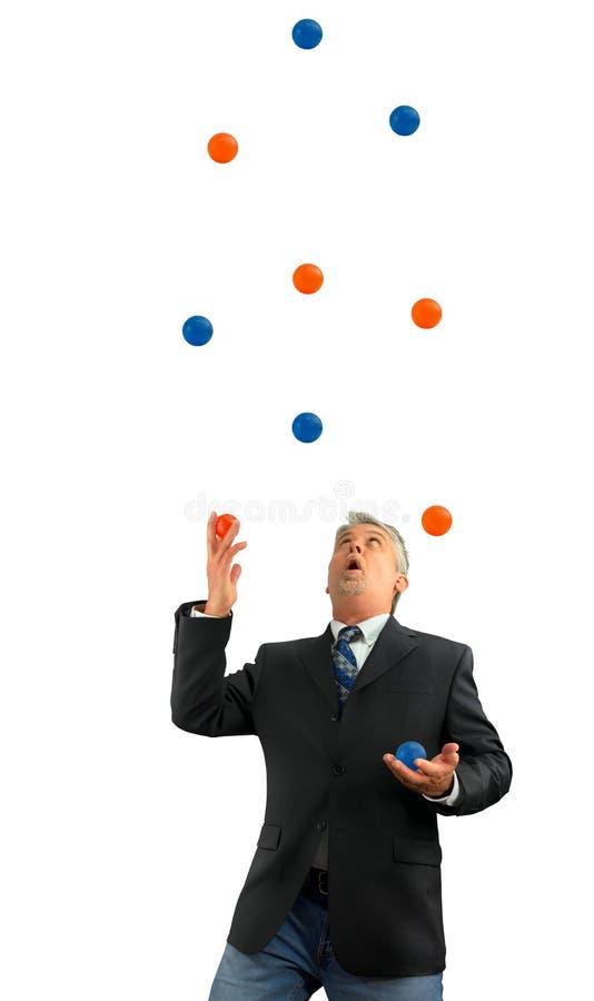 Homem que manipula muitas diversas bolas no ar que representa sendo ocupado na vida e no negócio com diversas coisas fatigantes imagens de stock royalty free