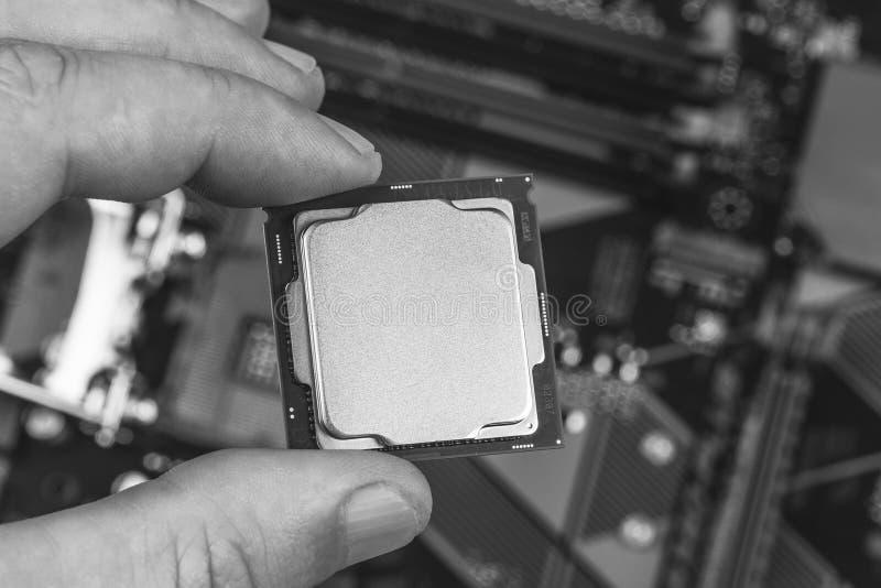 Homem que mantém os dedos trocistas acima gen do processador desktop do 8o na opinião superior do close up do cartão-matriz do fu fotos de stock