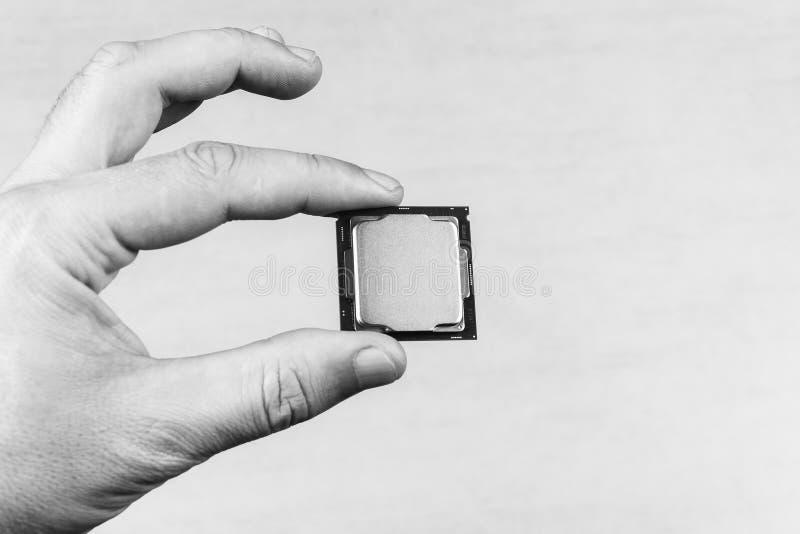 Homem que mantém os dedos trocistas acima gen do processador desktop do 8o na opinião superior do close up cinzento do fundo fotos de stock