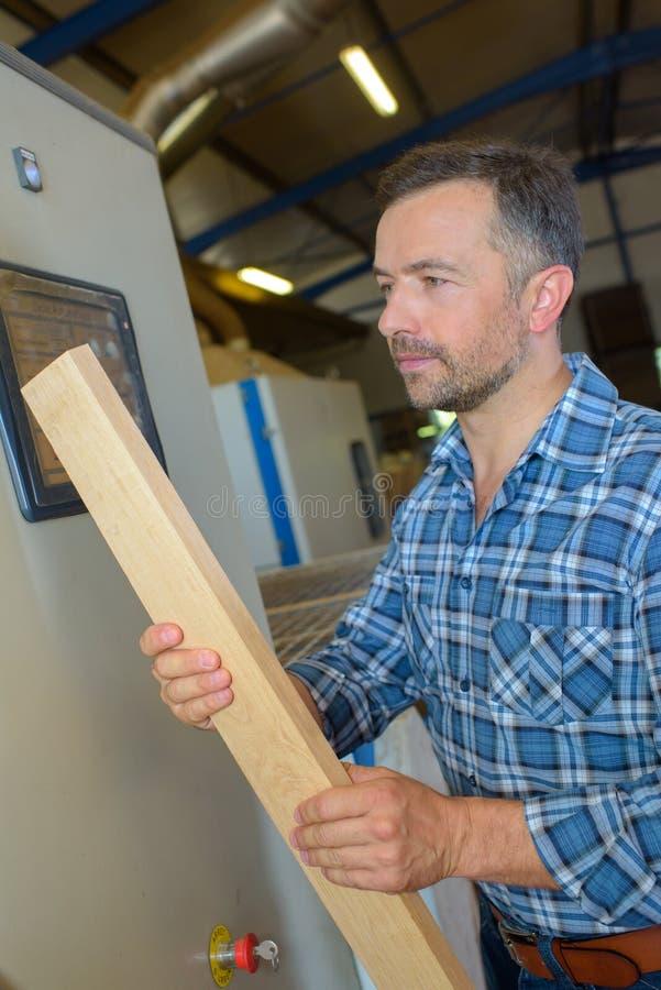 Homem que mantém a prancha de madeira imagem de stock