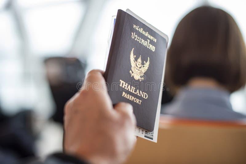 Homem que mantém um passaporte de Tailândia com uma passagem de embarque unido fotografia de stock royalty free