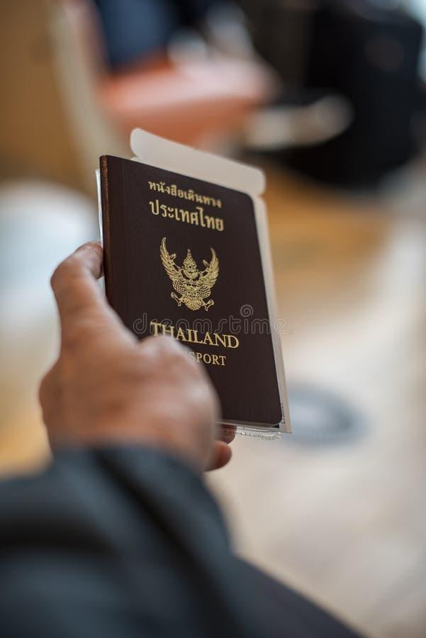 Homem que mantém um passaporte de Tailândia com uma passagem de embarque unido imagens de stock royalty free