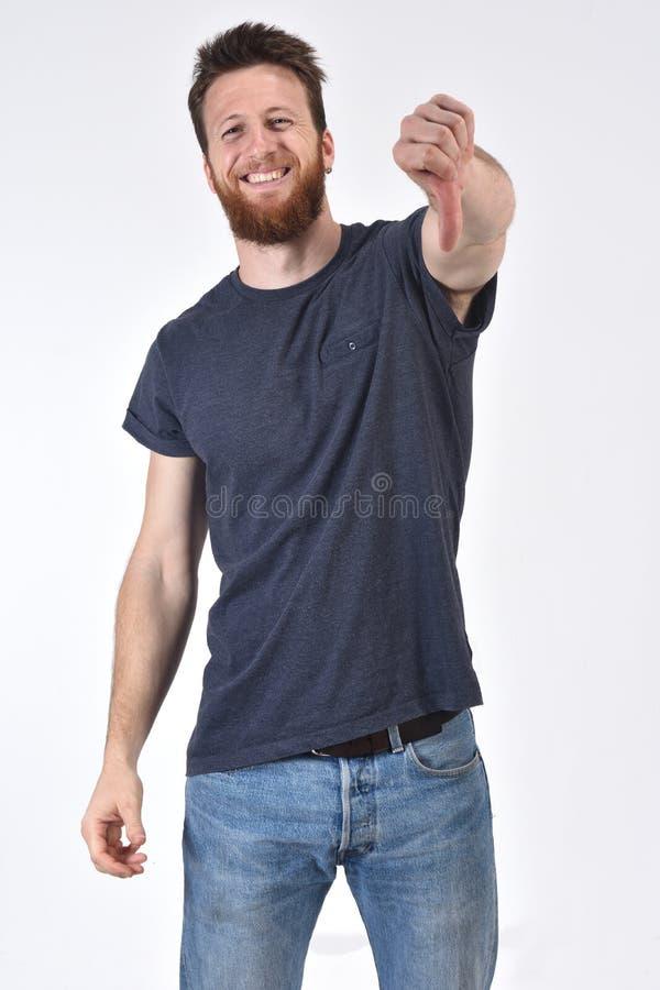 Homem que mantêm seu polegar e sério no fundo branco, sorrindo foto de stock