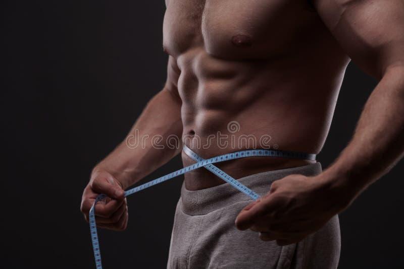 Homem que mede sua cintura com uma fita métrica foto de stock royalty free