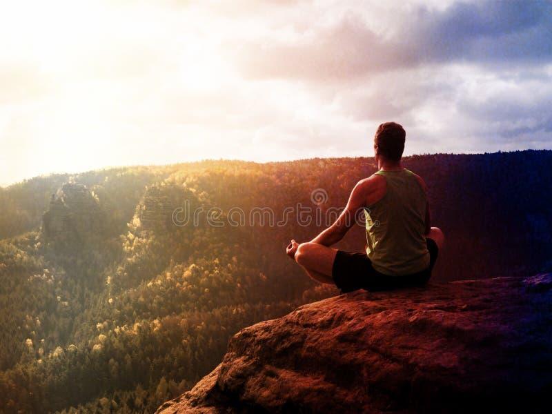 Homem que medita em Lotus Pose no penhasco rochoso Ioga praticando do desportista no pico fotos de stock royalty free