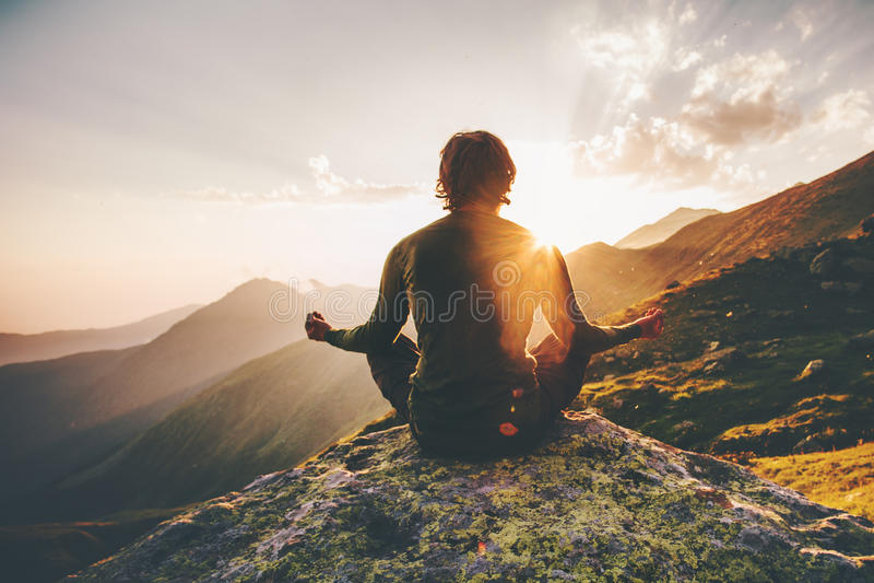 Homem que medita a ioga em montanhas do por do sol fotos de stock royalty free