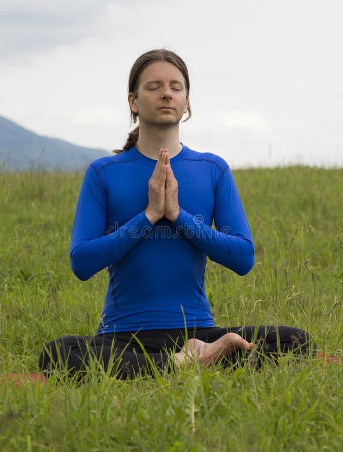 Homem que meditating ao ar livre imagem de stock