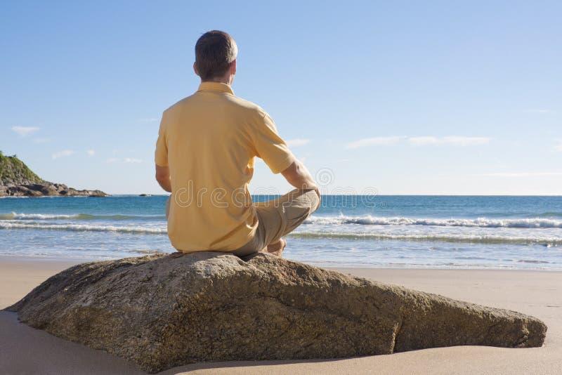 Homem que meditating em uma praia imagens de stock royalty free