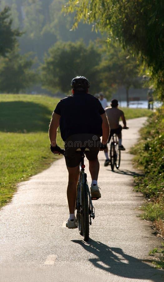 Homem que monta sua bicicleta foto de stock