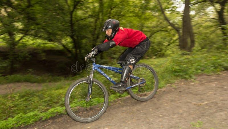Homem que monta um estilo em declive da bicicleta de montanha imagens de stock