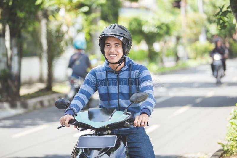 Homem que monta um motorcyle ou um velomotor imagem de stock royalty free