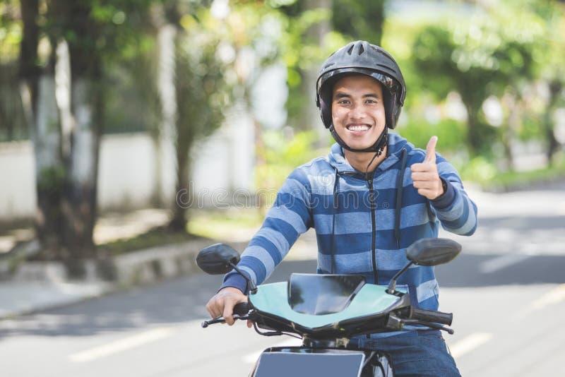 Homem que monta um motorcyle ou um velomotor imagens de stock royalty free