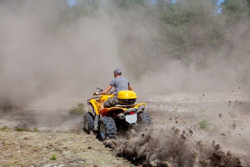 Homem que monta um quadrilátero amarelo ATV todo o veículo do terreno em um movimento extremo do esporte da floresta arenosa, ave imagens de stock