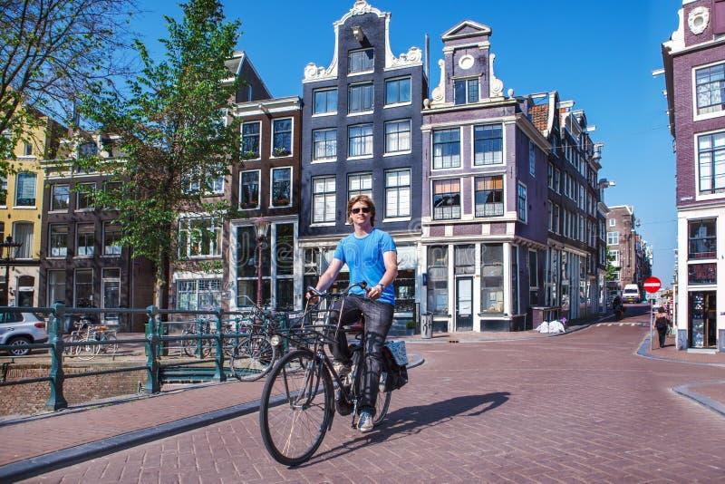 Homem que monta uma bicicleta em Amsterdão imagem de stock