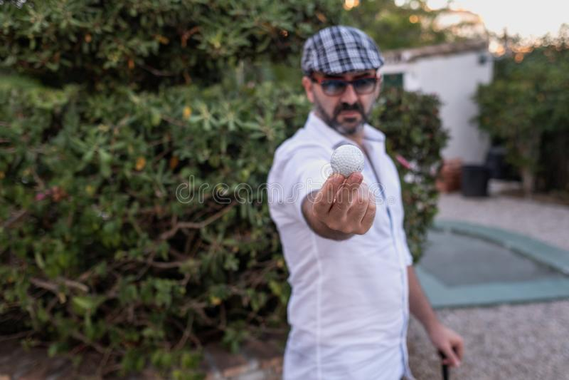 Homem que mostra a bola de golfe em suas mãos fotografia de stock