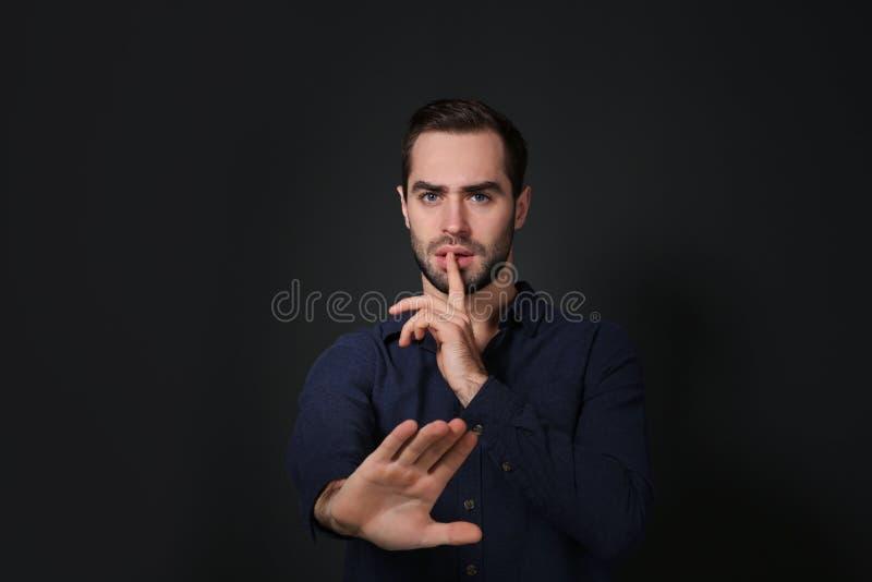 Homem que mostra o gesto do SIL?NCIO na linguagem gestual no preto foto de stock royalty free