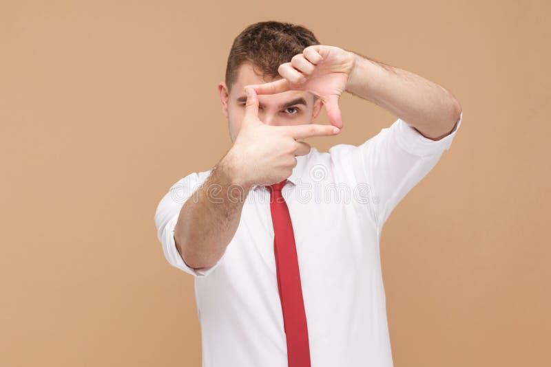Homem que mostra o sinal do fotógrafo do quadro na câmera fotos de stock royalty free