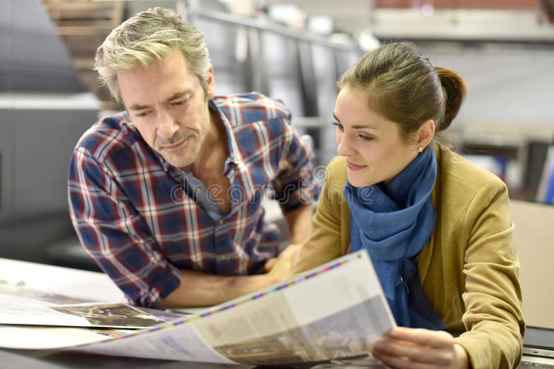 Homem que mostra a produção da impressão ao cliente fotos de stock