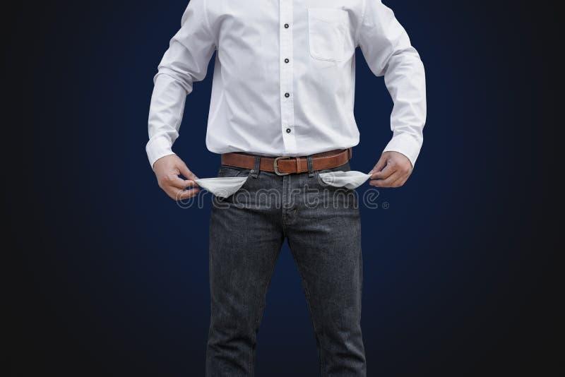 Homem que mostra seus bolsos vazios no fundo da parede imagens de stock