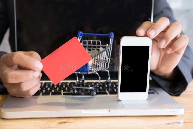 Homem que mostra um cartão de crédito e um telefone esperto móvel com supermark imagem de stock royalty free