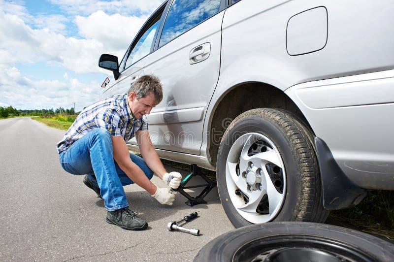 Homem que muda um pneu de reposição do carro fotografia de stock royalty free