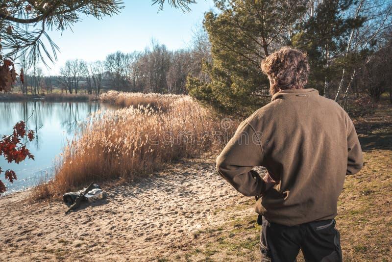 Homem que negligencia um lago na luz do sol fotografia de stock royalty free