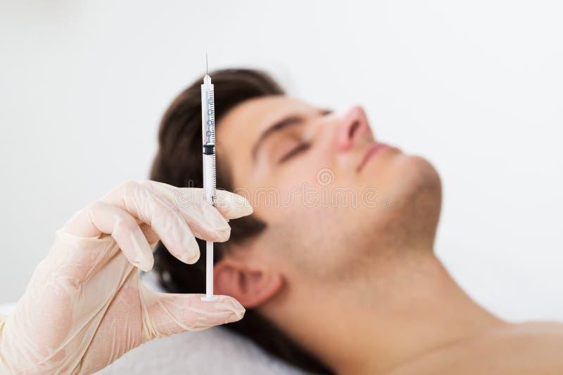 Homem que obtém o tratamento do enrugamento do doutor imagens de stock royalty free