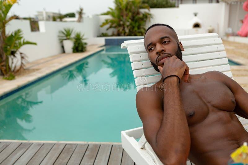 Homem que olha afastado ao relaxar em um vadio do sol perto da piscina no quintal da casa imagens de stock
