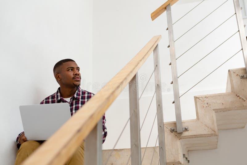 Homem que olha afastado ao trabalhar no portátil em escadas em uma casa confortável imagens de stock royalty free