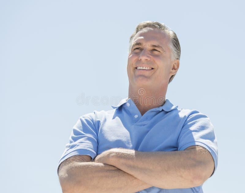 Homem que olha afastado com os braços cruzados contra o céu claro fotografia de stock royalty free