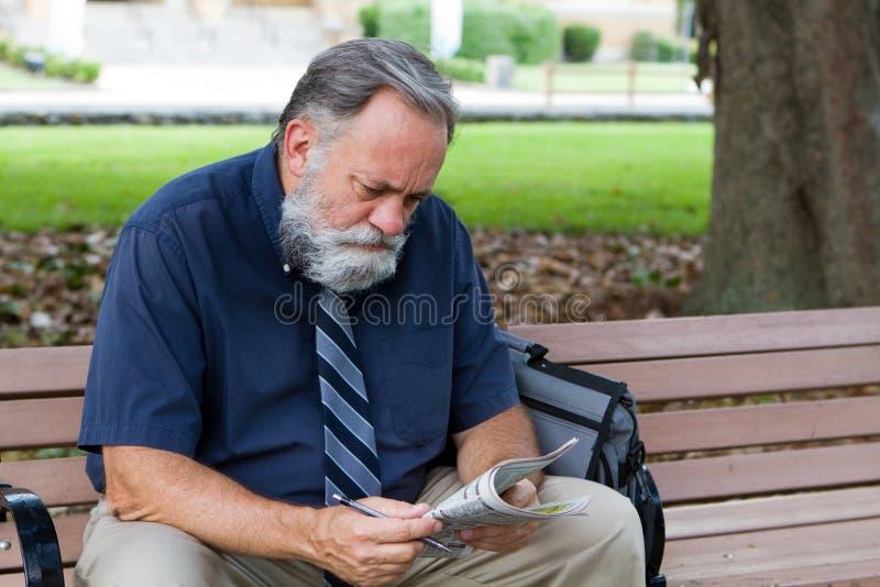 Homem que olha anúncios do trabalho imagem de stock royalty free