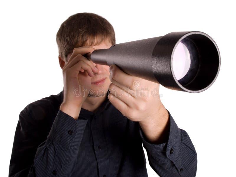 Homem que olha através de um telescópio fotos de stock royalty free