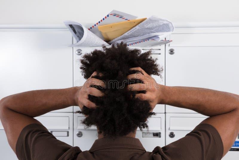 Homem que olha a caixa postal sobrecarregada com os correios nãos solicitados fotos de stock royalty free