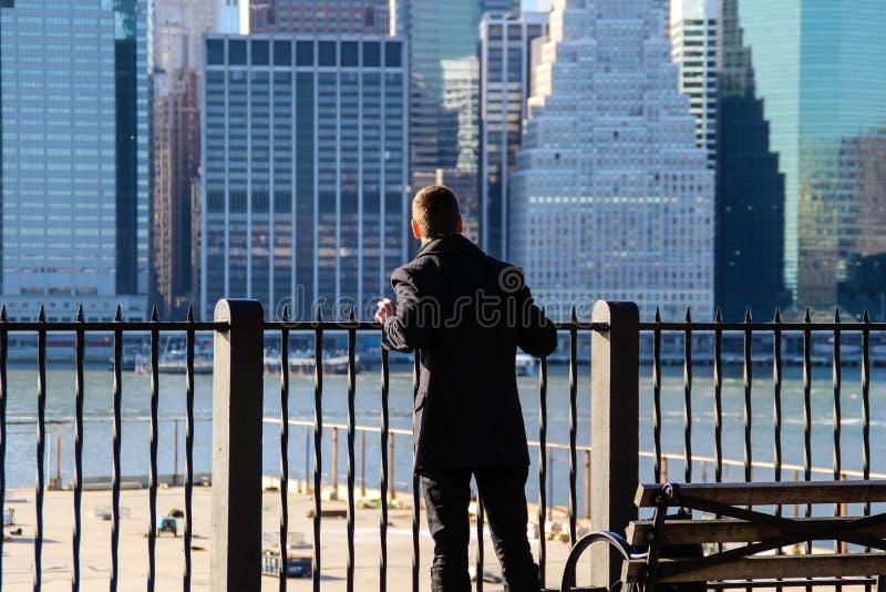 Homem que olha em Manhattan de Brooklyn imagens de stock royalty free