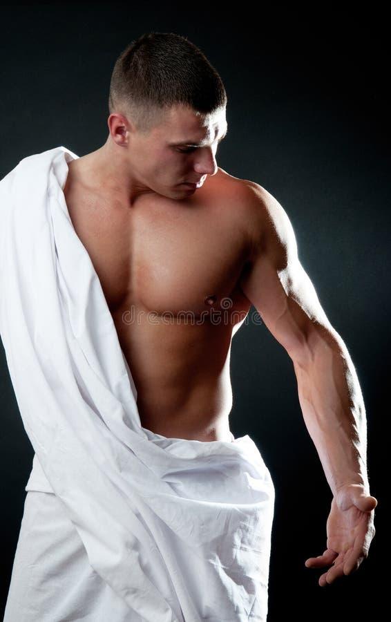 Homem que olha em seu bíceps imagens de stock