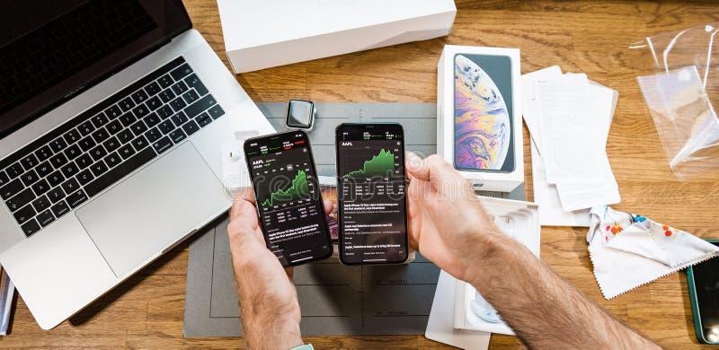Homem que olha a evolução do mercado de valores de ação de AAPL no iPhone XS imagens de stock