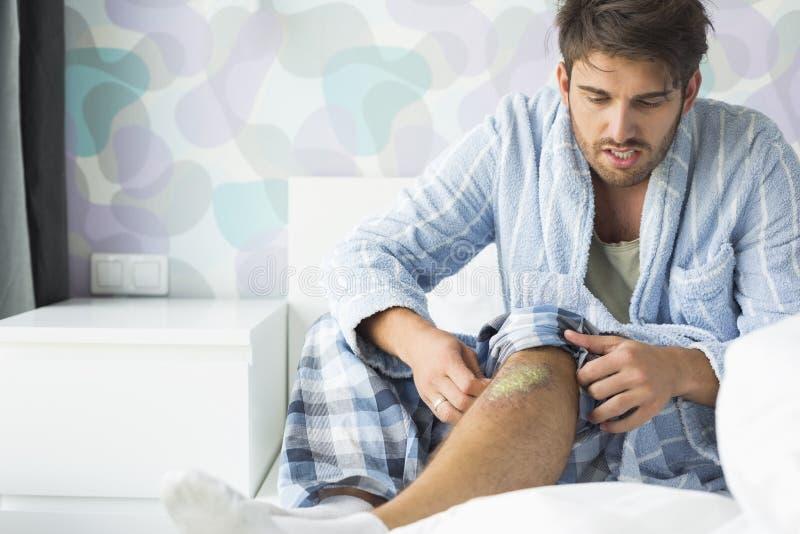 Homem que olha a ferida na cama em casa foto de stock royalty free