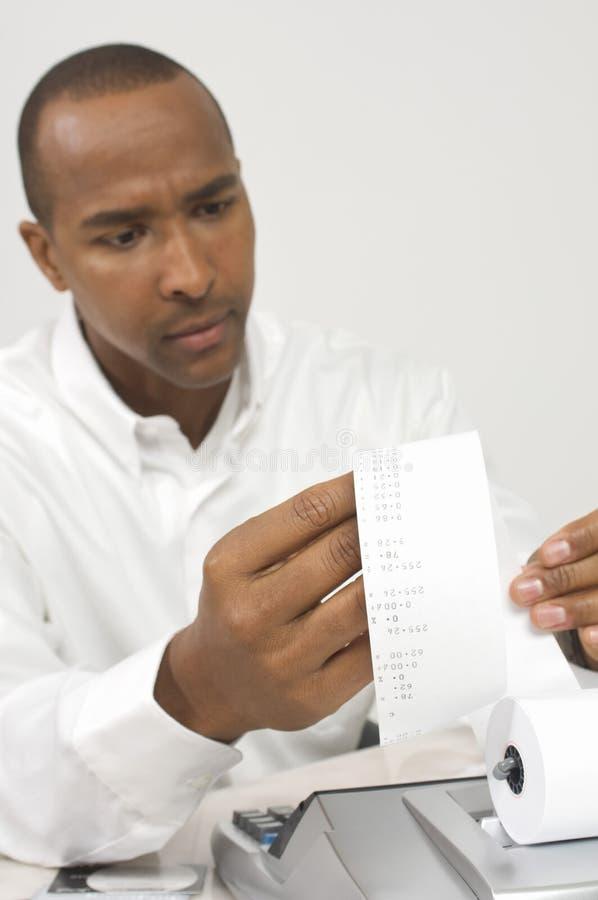 Homem que olha a fita da calculadora fotografia de stock
